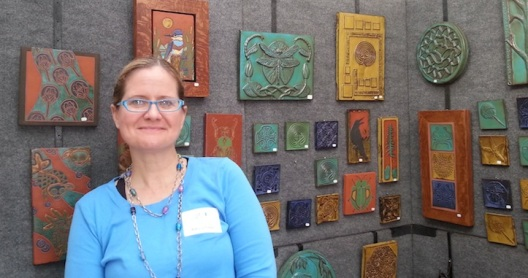 Patricia Tolton poses with her pottery at the Outdoor Show